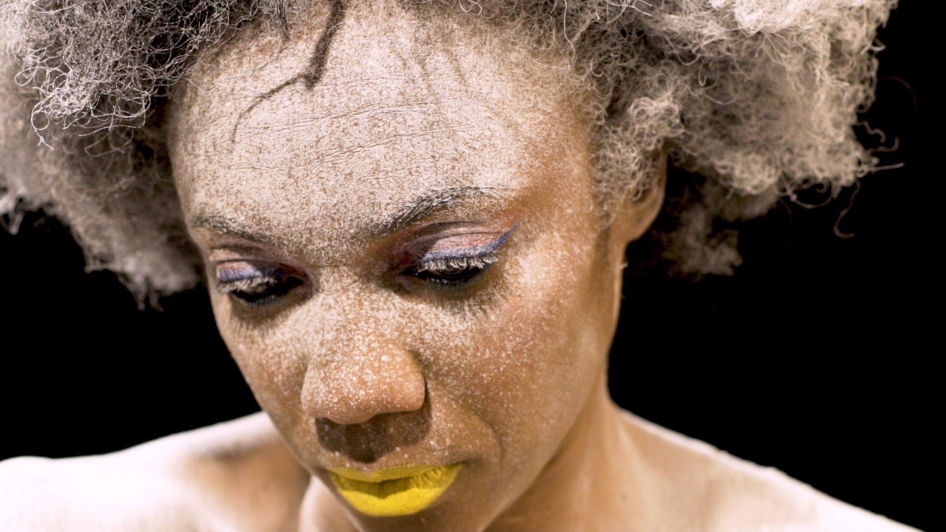 A woman with powder on her face and yellow-painted lips looks down mournfully.