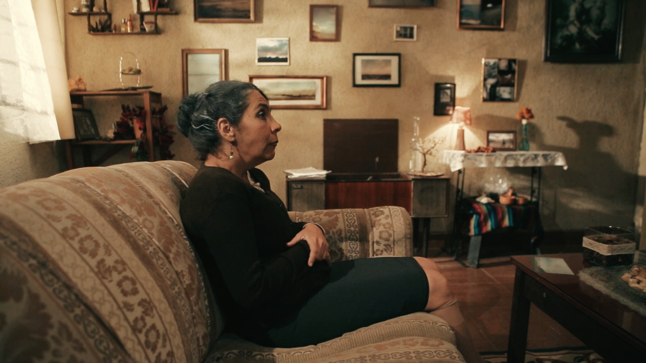 An older woman sits cross-armed on the couch of a living room.